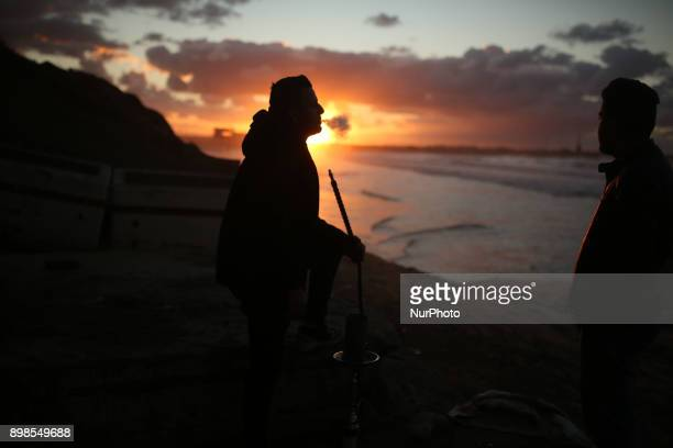 A Palestinian youth smoke waterpipe by the beach at sunset in Gaza City on December 25 2017