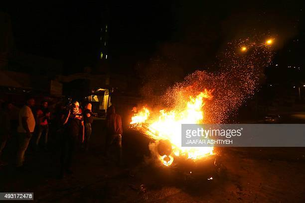 Palestinian youth stand next to a burning car belonging to an Israeli settler that was set on fire by Palestinians as it entered the northern...