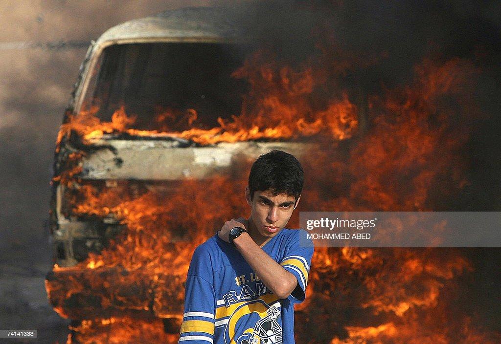A Palestinian youth stands in front of a... : Fotografía de noticias