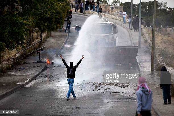Palestinian youth stands in front of an Israeli police water cannon on May 13, 2011 in the East Jerusalem neighbourhood of Issawiya, Israel....