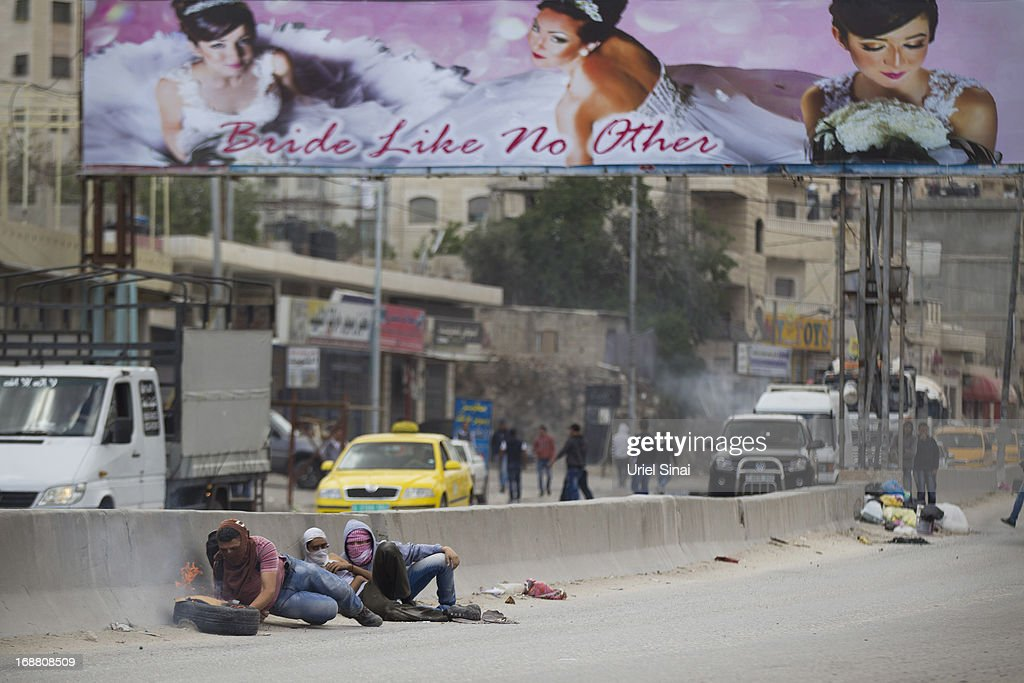 Palestinian youth take cover during clashes with the Israeli army during Nakba day on May 15, 2013 near the Qalandia checkpoint at the outskirts of Ramallah, the West Bank. Palestinians mark Israel's establishment in 1948 with 'Nakba' or 'catastrophe' day on May 15, to remember the thousands of Palestinians who fled or were expelled during the creation of the Jewish state and the subsequent war.