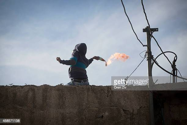 Palestinian youth throw a molotov cocktail during clashes with police after noon prayer on November 7 2014 in Jerusalem Israel A Palestinian resident...