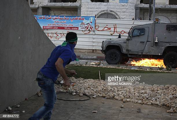 A Palestinian youth throws a Molotov cocktail at an Israeli security forces vehicle during clashes in Beit El Jewish settlement north of Ramallah in...