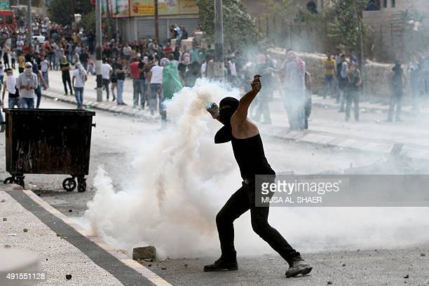 A Palestinian youth throws a tear gas canister back towards Israeli security forces during clashes at the main entrance of the West Bank town of...