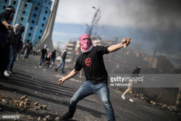 Palestinian youth throws rocks at Israeli Defence Forces in the streets on December 11 2017 in North of Ramallah WestBank Protest continues into the...