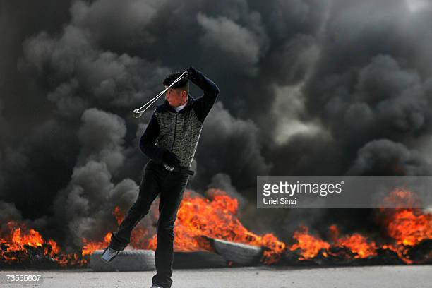 Palestinian youth throws stones at Israeli soldiers during clashes at an Israeli military checkpoint between Jerusalem and the West Bank city of...