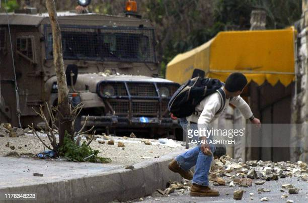 A Palestinian youth throws stones to an Israeli army vehicle during a military operation in the West Bank city of Nablus 11 April 2006 Israel's...