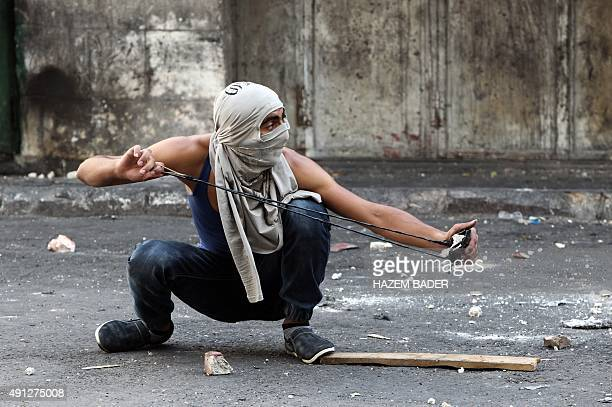 A Palestinian youth throws stones using a sling shot towards Israeli security forces during clashes in the West Bank town of Hebron on October 4...