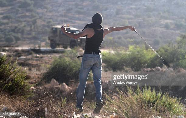 Palestinian youth uses a slingshot to hurl stones towards Israeli soldiers during clashes following a protest against the expropriation of...