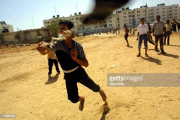 Palestinian youth uses a slingshot to throw stones towards an Israeli tank during clashes September 28 2002 in the Gaza Strip town of Bet Laheya near...