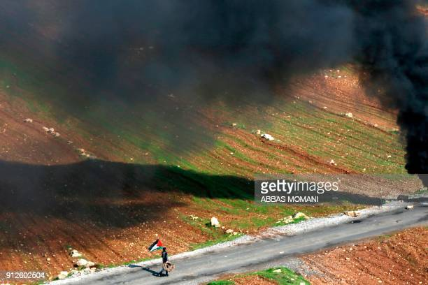Palestinian youth walks holding his national flag during clashes with Israeli soldiers in the village of Mugheer about 25 kilometres northeast of the...
