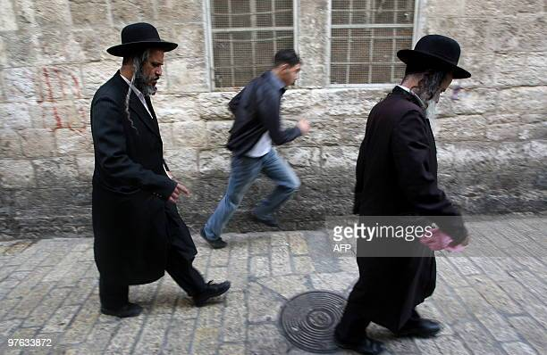 A Palestinian youth walks past Jewish UltraOrthodox men in Jerusalem's Old City's on March 11 2010 Israeli Prime Minister Benjamin Netanyahu issued a...
