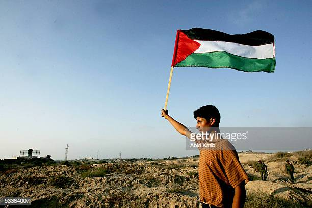 Palestinian youth waves a Palestinain national flag in front of the Israeli settlement of Navi Dakalem during early celebrations of Israel's imminent...