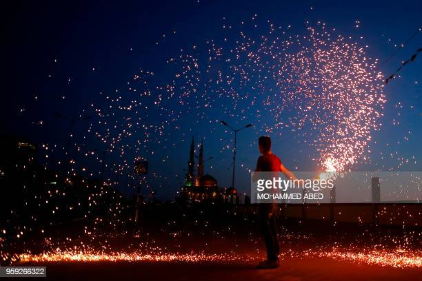 Palestinian youth waves a sparkler next a mosque in Gaza City on May 16 as the faithful prepare to start the Muslim holy fasting month of Ramadan