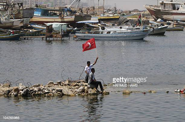A Palestinian youth waves a Turkish falg at the Mediterranean port of Gaza City on May 31 following a deadly Israel military raid on a Gazabound...