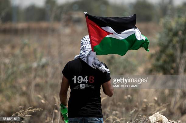 Palestinian youth waves the national flag as Israeli military digs in search of smuggling tunnels at the border east of Gaza city on May 15 on the...