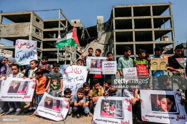 Palestinian youths and children demonstrate with Palestinian flags in Gaza City on July 15 2018 outside a building that was struck by an Israeli air...