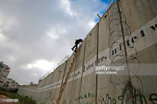 Palestinian youths climb a section of Israel's separation wall to reach at the al-Aqsa Mosque compound in Jerusalem on May 10, 2019 near Ramallah in...