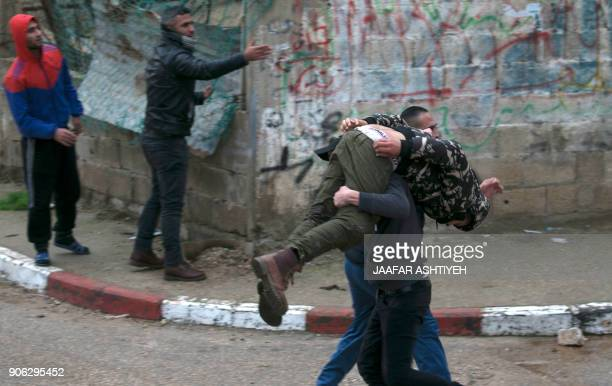 TOPSHOT Palestinian youths evacuate a wounded comrade during clashes with Israeli forces in Jenin in the north of the occupied West Bank on January...