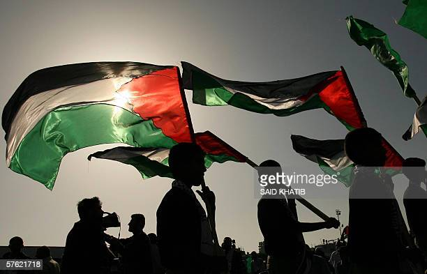 Palestinian youths hold national flags during a Hamas rally held to mark the 58th anniversary of the Naqba 15 May 2006 in the southern Gaza Strip...