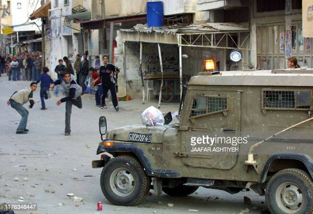 Palestinian youths hurl stones at Israeli army jeep in the refugee camp of Balata in the West Bank city of Nablus 30 November 2003 during an Israeli...