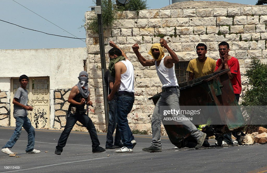 Palestinian youths hurl stones at Israeli troops during a demonstration in the West Bank village of Nabi Saleh on May 21, 2010 against the expansion of the nearby Jewish settlement of Halamish in the occupied West Bank. Israeli forces shot dead two Palestinian gunmen who had just infiltrated Israel from the Gaza Strip, the military said.