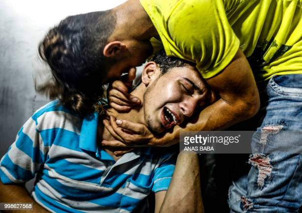 TOPSHOT Palestinian youths mourn at alShifa hospital morgue on July 14 2018 after two teenagers were killed in one of a series of Israeli raids Aged...
