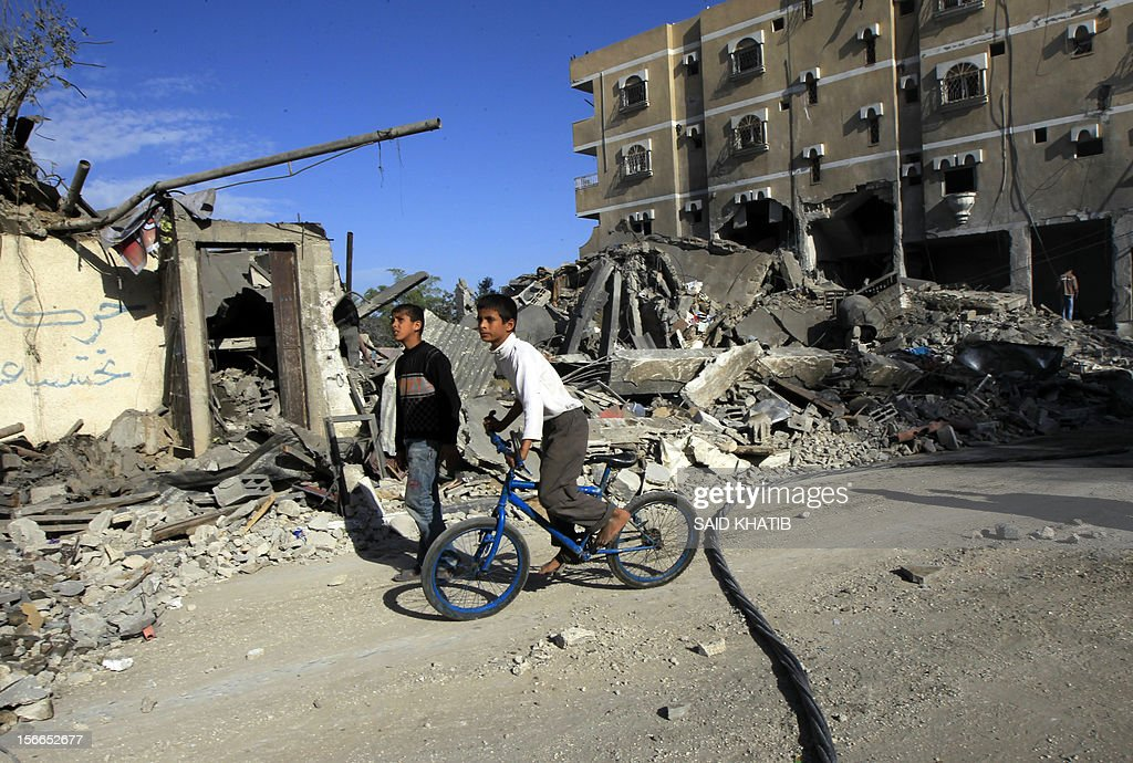 Palestinian youths pass destroyed buildings following Israeli air strikes on the southern Gaza Strip town of Rafah on November 18, 2012. Israeli war planes hit a Gaza City media centre and homes in northern Gaza in the early morning, as the death toll mounted, despite suggestions from Egypt's President Mohamed Morsi that there could be a 'ceasefire soon.'