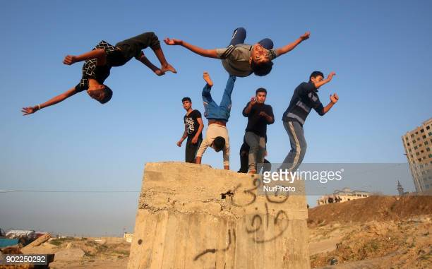 Palestinian youths practice parkour by the beach at sunset in Gaza City on City January 7 2018