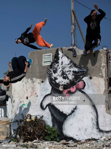 Palestinian youths practice their Parkour skills past a mural said to have been painted by British street artist Banksy on the remains of a house...