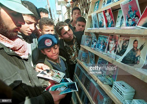 Palestinian youths purchase pictures of Palestinian Resistance Movement fighters February 1 2002 killed by Israeli forces during an uprising against...