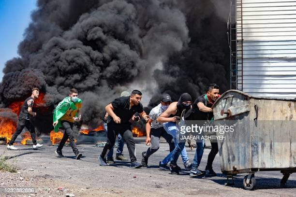 Palestinian youths push a rubbish container used as a barricade, during confrontations with Israeli security forces near the Hawara checkpoint south...
