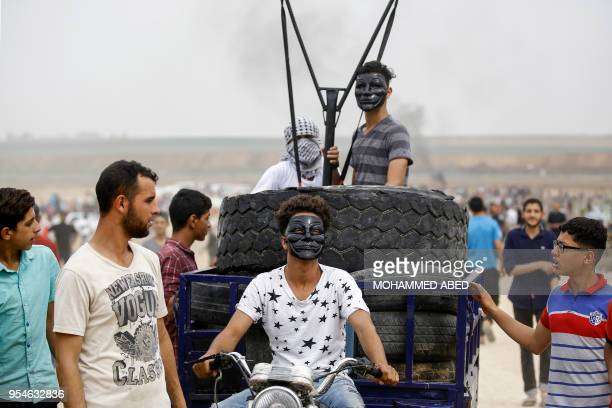 Palestinian youths ride in the back of a motorcycle cart carrying tires to be burned and a small catapult to hurl stones towards Israeli forces,...