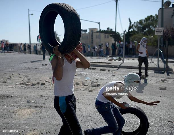Palestinian youths roll tires towards Israeli security forces during the clashes over the abduction and killing of a Palestinian teen by suspected...