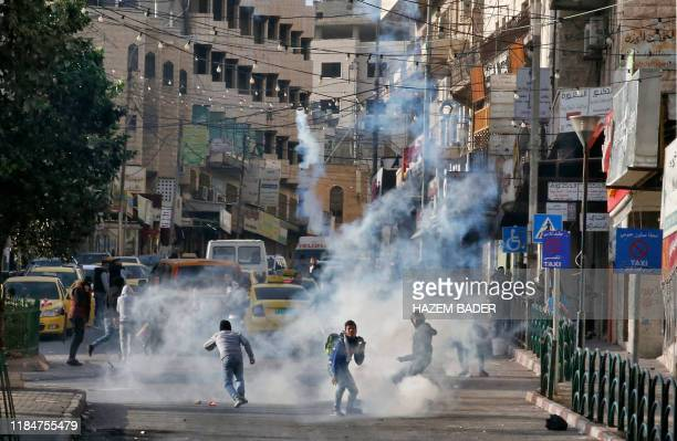 TOPSHOT Palestinian youths run from tear gas smoke fired by Israeli security forces on November 26 2019 during clashes in the West Bank city of...