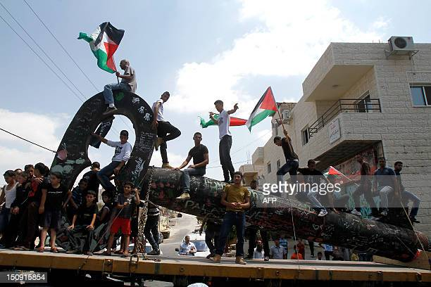 Palestinian youths sit on the 'The Key of Return' which was exhibited at the seventh Berlin Biennale upon its return to the Aida refugee camp near...
