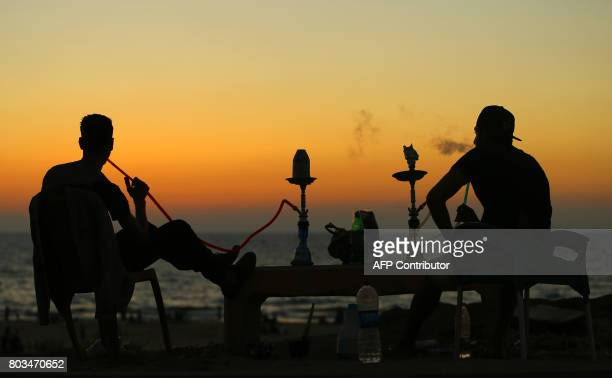 Palestinian youths smoke waterpipe by the beach at sunset in Gaza City on June 29 2017 / AFP PHOTO / MOHAMMED ABED