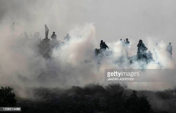 Palestinian youths stand amidst tear gas smoke during clashes with Israeli forces in a village south of Nablus in the occupied West Bank on March 11,...