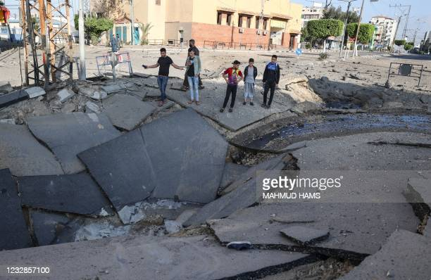 Palestinian youths take pictures with their smart phones of a huge crater on a main road in Gaza City on May 13, 2021 following continued Israeli...