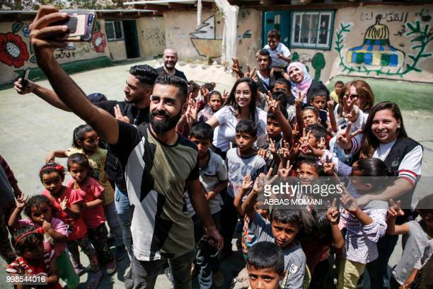 Palestinian youths take 'selfie' photographs with their phones alongside children from the Bedouin village of Khan alAhmar in the occupied West Bank...