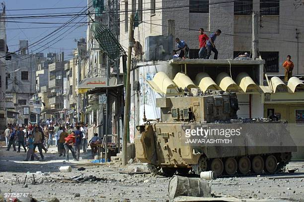 Palestinian youths throw stones at an Israeli armored vehicle in the West Bank city of Nablus 03 June 2003 Israeli Prime Minister Ariel Sharon and...