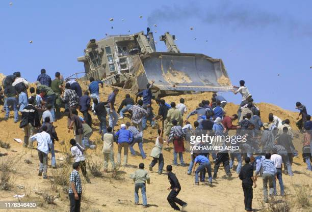 Palestinian youths throw stones at an Israeli army bulldozer in Beit Lahia in the northern Gaza Strip, 22 April 2004. For the third consecutive day...