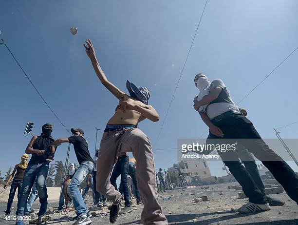 Palestinian youths throw stones at Israeli security forces during the clashes over the abduction and killing of a Palestinian teen by suspected...