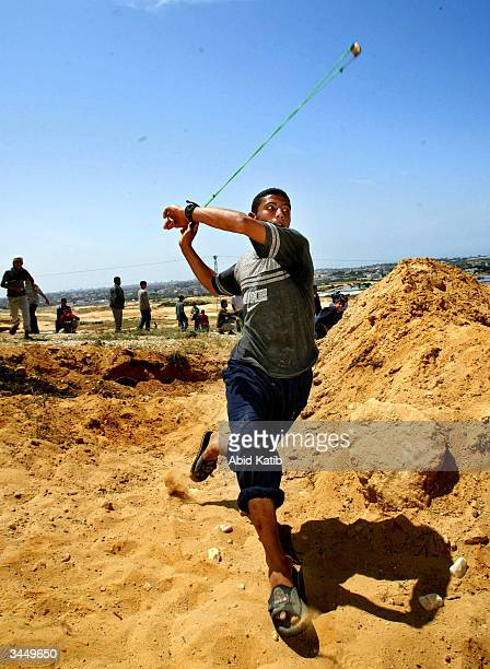 Palestinian youths throw stones at Israeli tanks and bulldozers during clashes with Israeli soldiers April 20 2004 near the Beit Lahyea Refugee Camp...