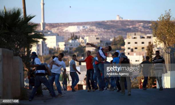 Palestinian youths throw stones towards Israeli soldiers during clashes following a protest against the Jewish settlements and the Israeli Wall of...
