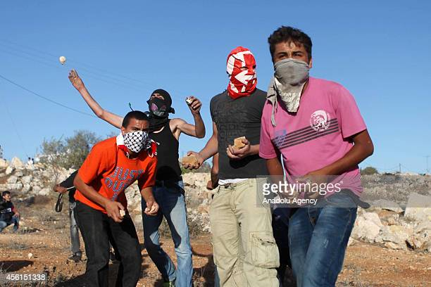 Palestinian youths throw stones towards Israeli soldiers during clashes following a protest against the expropriation of Palestinian land by Israel...
