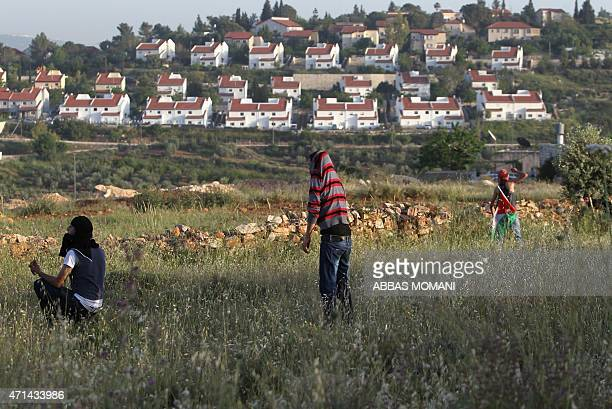 Palestinian youths throw stones towards members of the Israeli security forces during clashes after a the house belonging to a Palestinian family was...