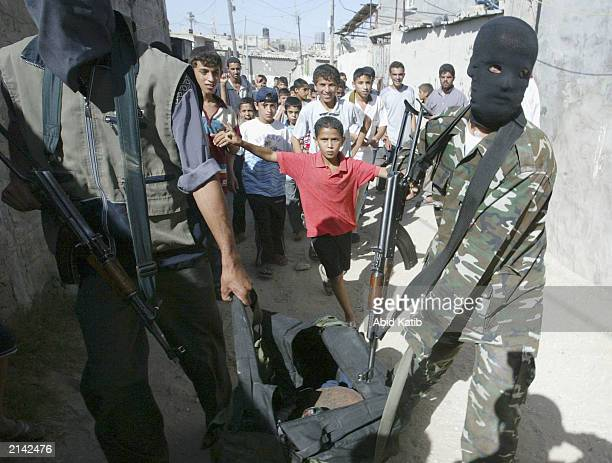 Palestinian youths watch masked Palestinian militant members of the Hamas group walk by, while they hold their guns and bombs July 7, 2003 in Rafah...