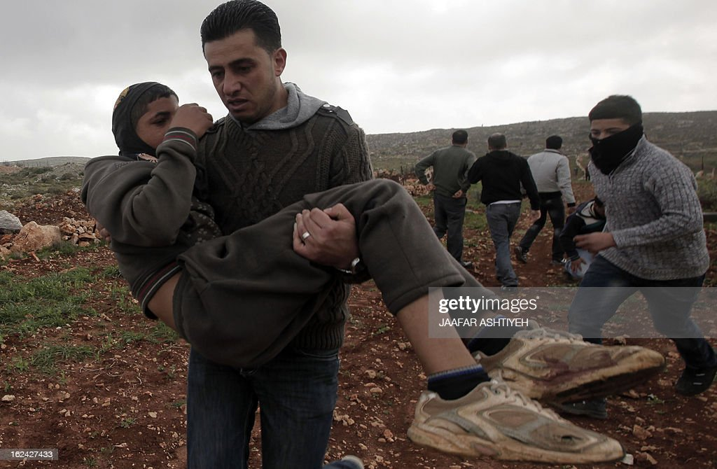 Palestinians aid a wounded proterstor following clashes with Israeli settlers in the West Bank village of Qusra near Nablus on February 23, 2013. Three Palestinians were wounded in clashes with Jewish settlers from a wildcat settlement near a village in the northern West Bank, various sources said.