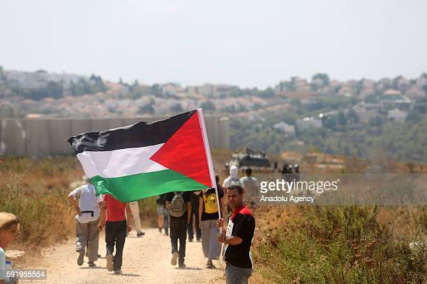 Palestinians and a group of activists hold Palestinian flags during a protest held to support the imprisoned Palestinians who stage hunger strike in...